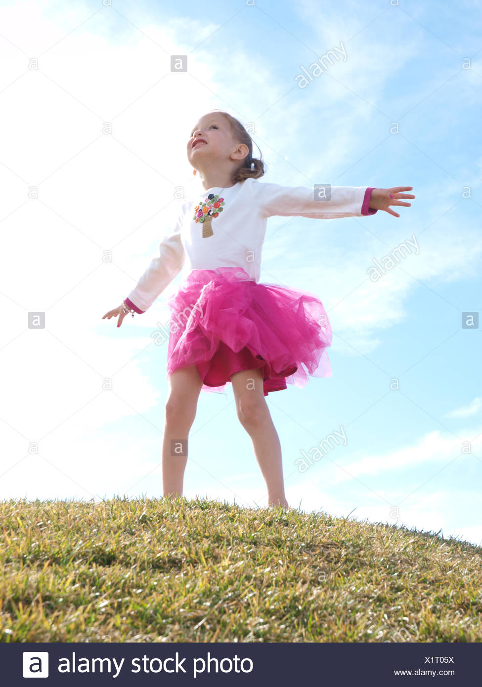 Girl Standing With Her Arms Outstretched - Stock Image