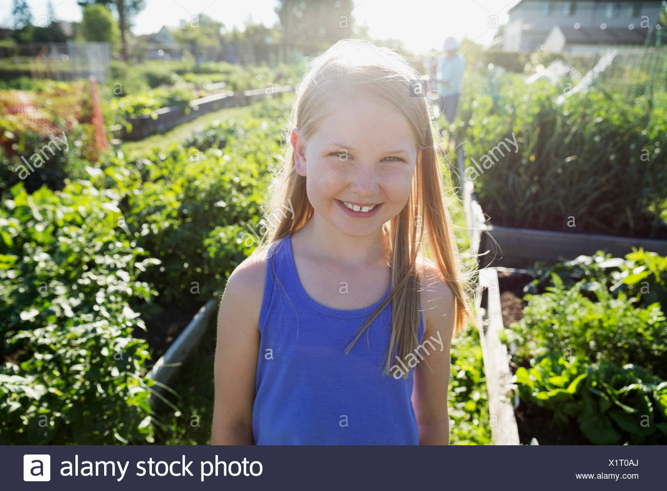 Portrait smiling girl in sunny garden - Stock Image