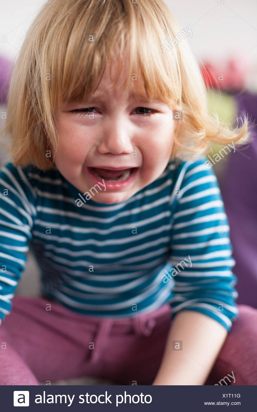 portrait of blonde two years old child with striped blue and white sweater sitting and crying looking. - Stock Image