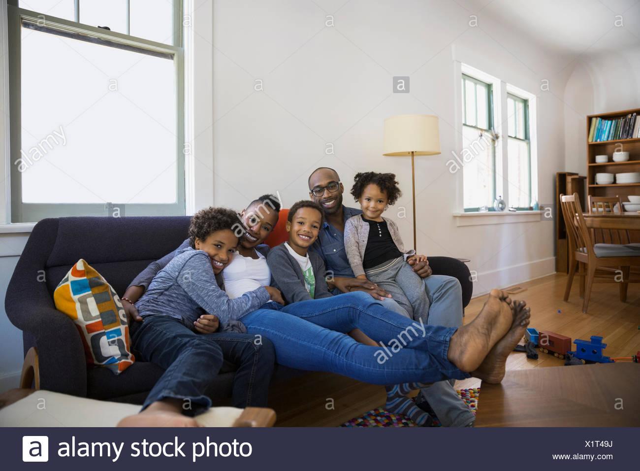 Portrait of smiling family on living room sofa - Stock Image