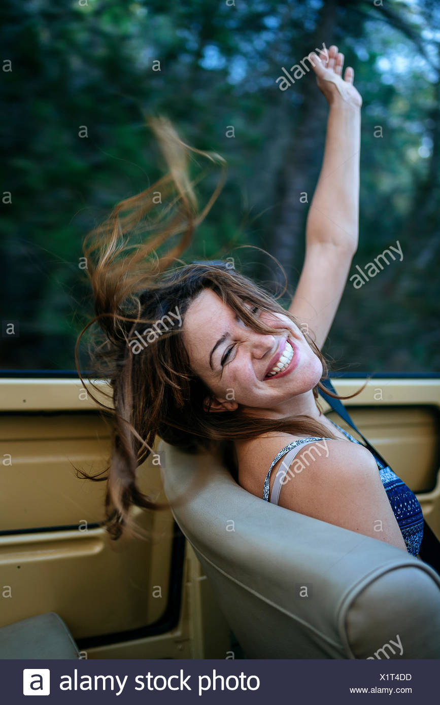 Happy woman siting in covertible - Stock Image