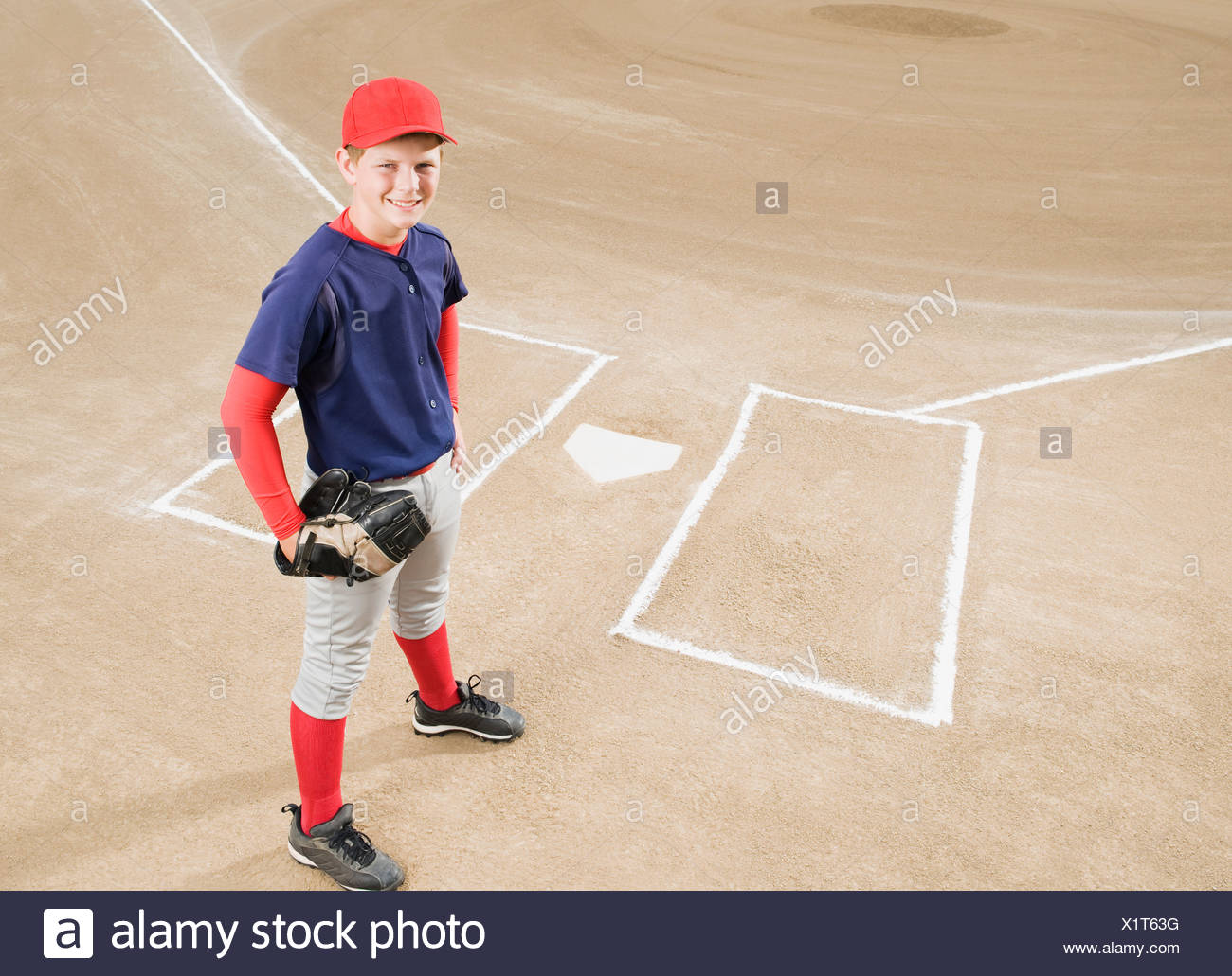 Baseball player in uniform posing by home plate Stock Photo