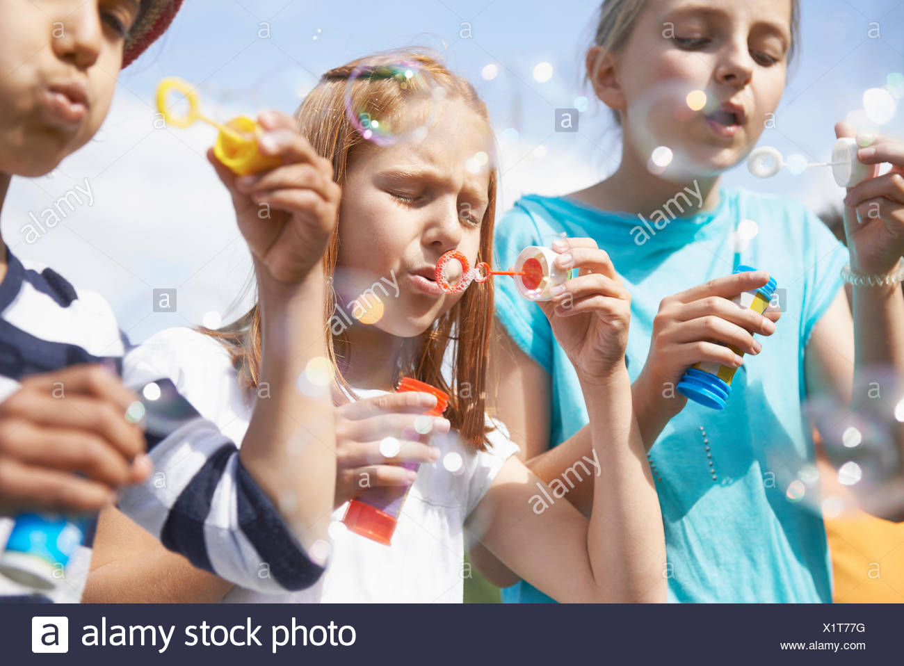 Girls blowing bubbles with bubble wands, Bavaria, Germany - Stock Image