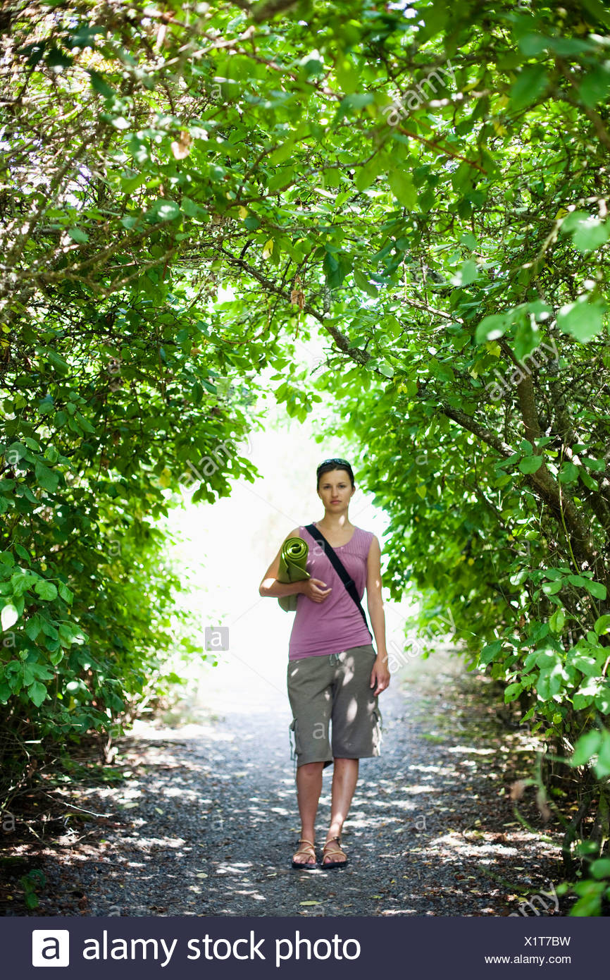 A young woman stands in an arch of greenery while holding her yoga mat. - Stock Image