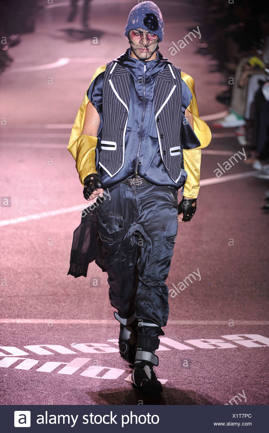 John Galliano Paris Menswear Spring Summer Model wearing baggy grey silk combat trousers, black and grey boots velcro straps, - Stock Image