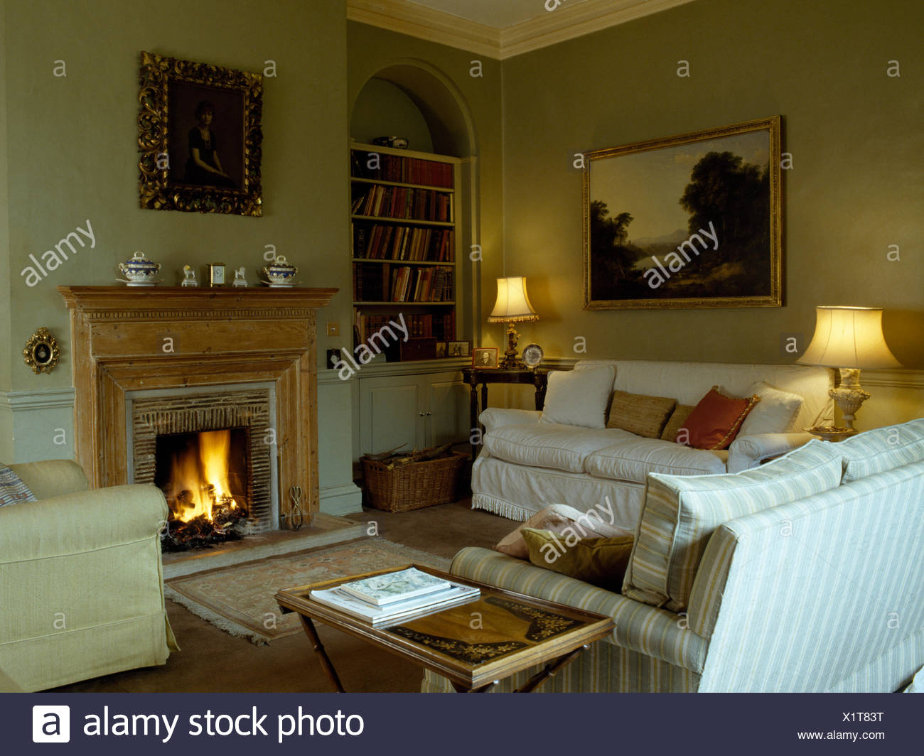 Comfortable sofas around fireplace with lighted fire in traditional style eighties sitting room Stock Photo