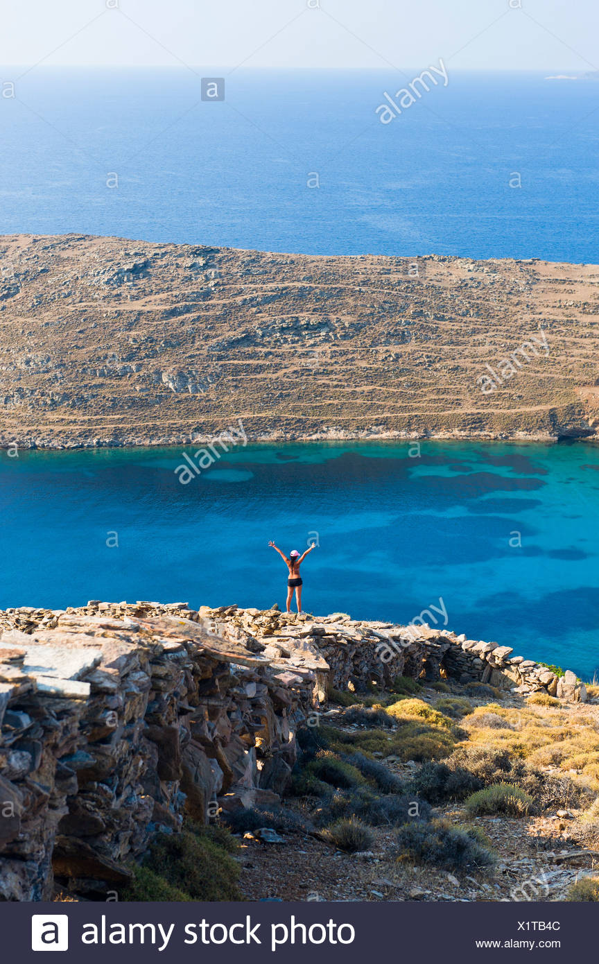 Mid distance rear view of a teenage girl in the archaic landscape with arms raised at Aegean sea - Stock Image