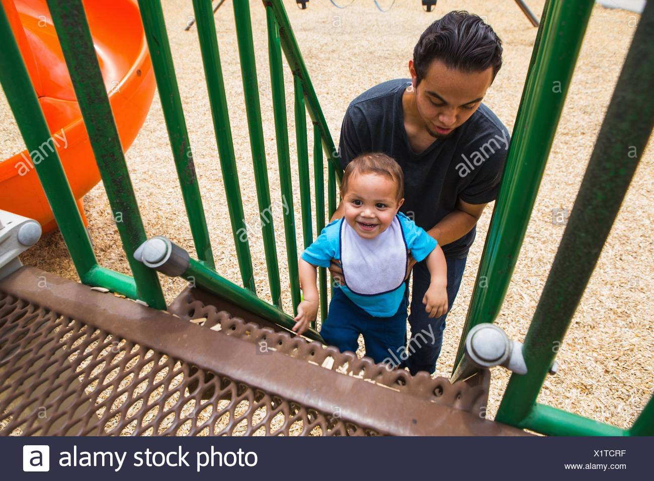 Young man guiding toddler brother up playground slide steps Stock Photo