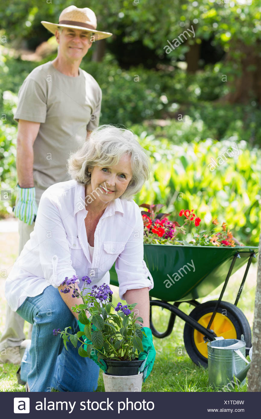 Mature woman engaged in gardening with man in background - Stock Image