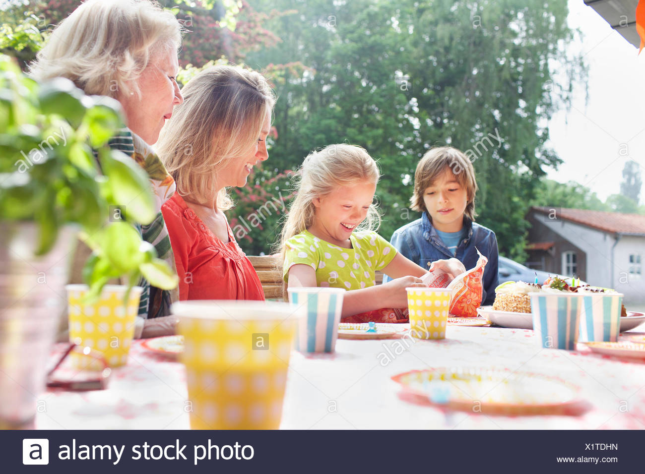 Girl opening birthday gift with her family at birthday party - Stock Image