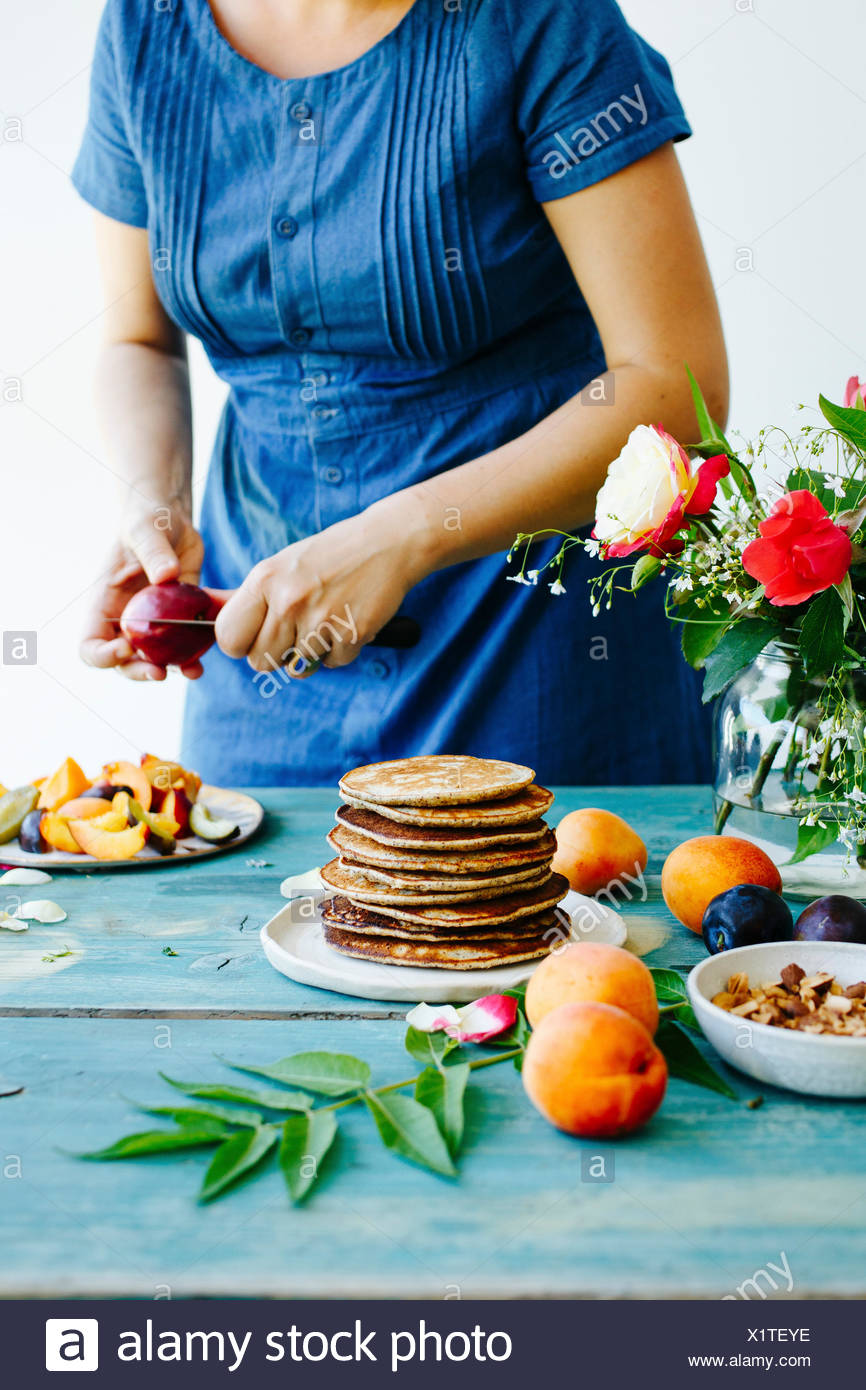 Pancakes on the wooden table and girl in denim dress behinde - Stock Image