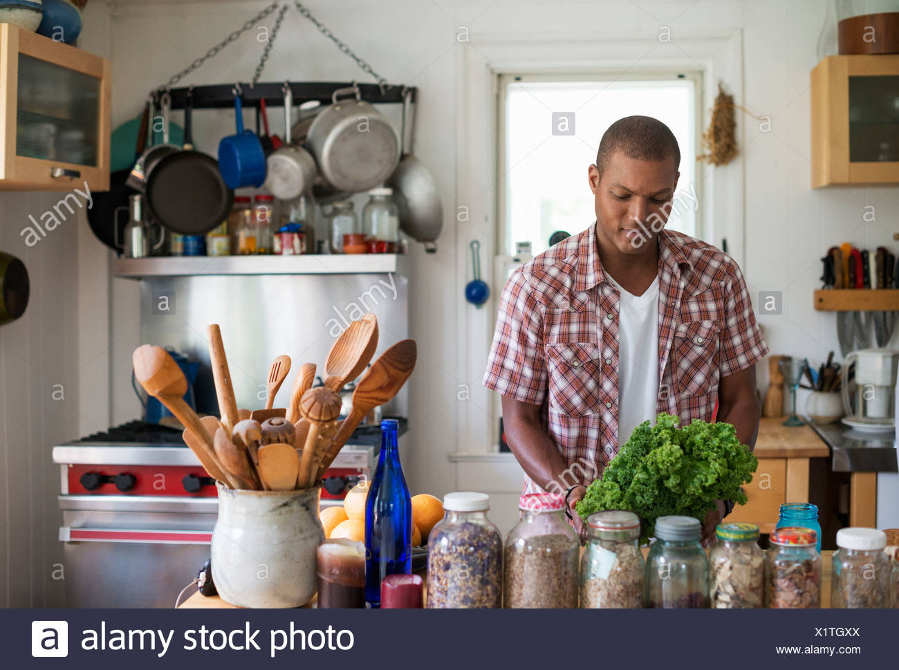 A young man in a kitchen preparing salad leaves and vegetables. - Stock Image