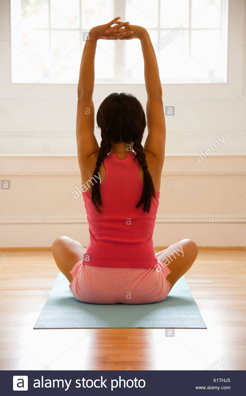 Rear view of young woman sitting on mat with legs crossed stretching - Stock Image