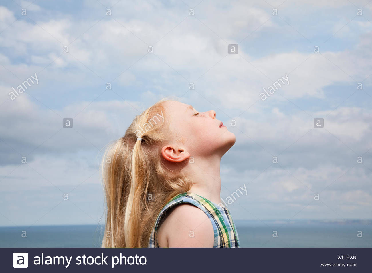 A young girl raising her face to the sun. - Stock Image