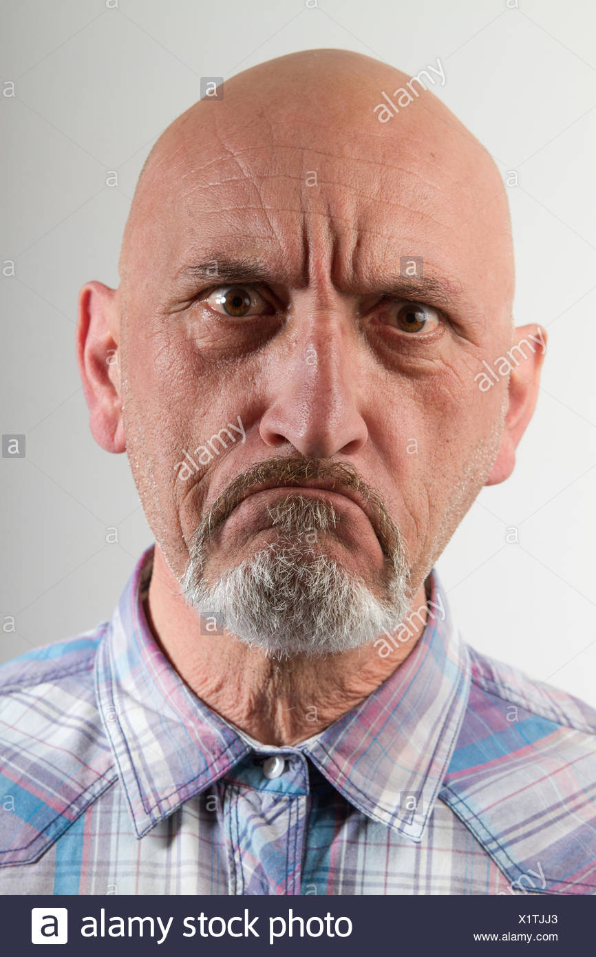 Close-Up Portrait Of Angry Man Against Gray Background Stock Photo