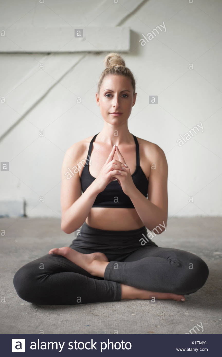 Mid adult woman meditating lotus pose in yoga studio, Munich, Bavaria, Germany - Stock Image
