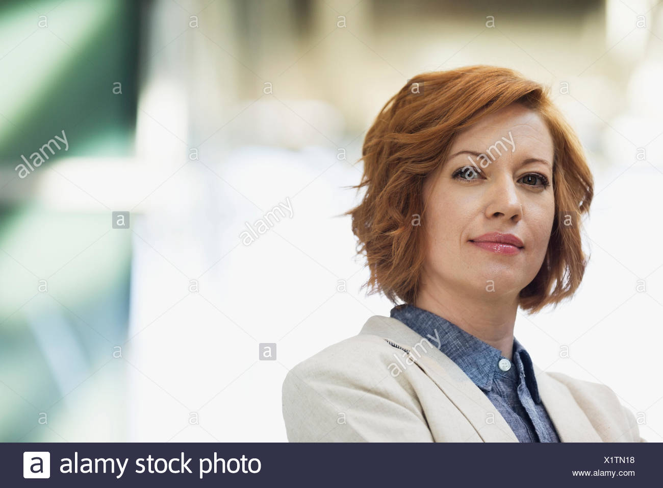 Portrait of confident red haired businesswoman - Stock Image