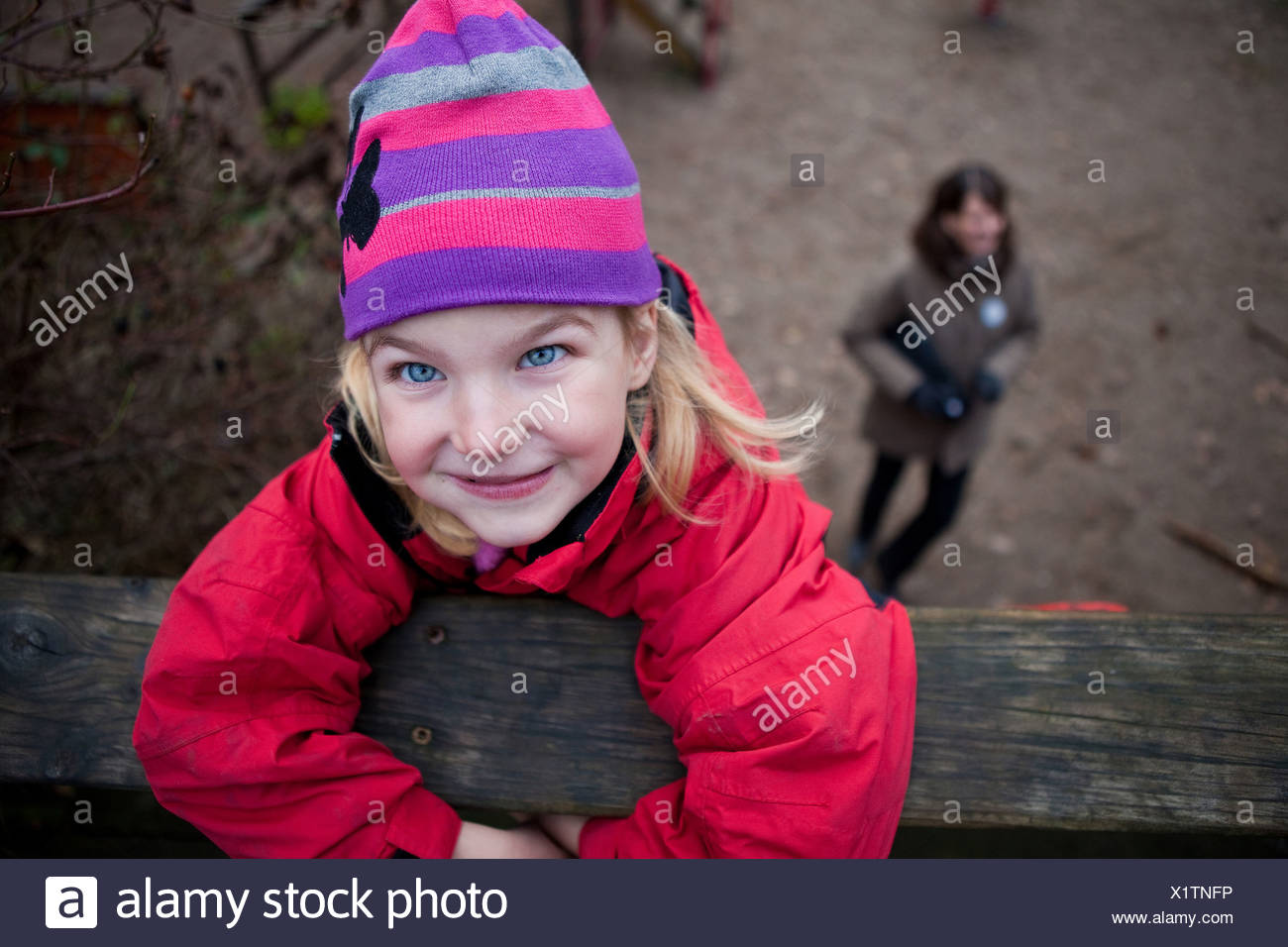 Portrait of a little girl in winter wear hanging on to a log with blurred woman in the background - Stock Image