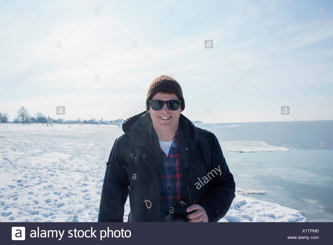 Portrait of mid adult man against snowy backdrop - Stock Image