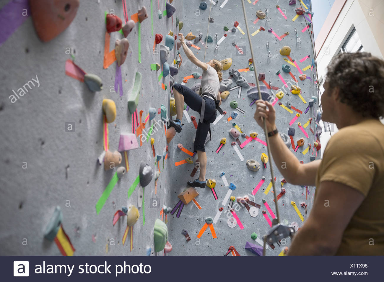 Man watching woman climb indoor rock wall - Stock Image