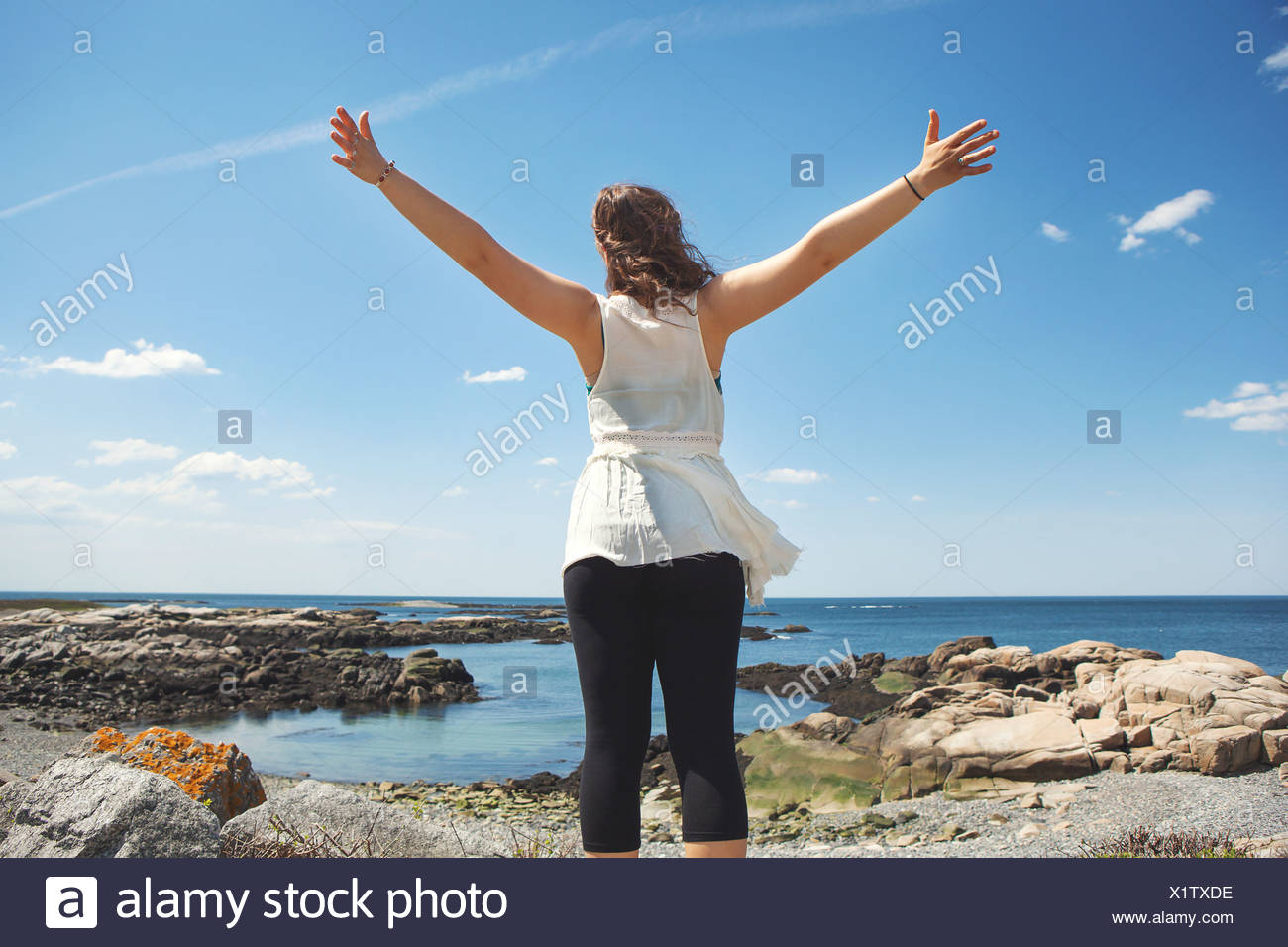 Rear view of young woman at the rocky coastal beach in Biddeford, Maine, USA - Stock Image