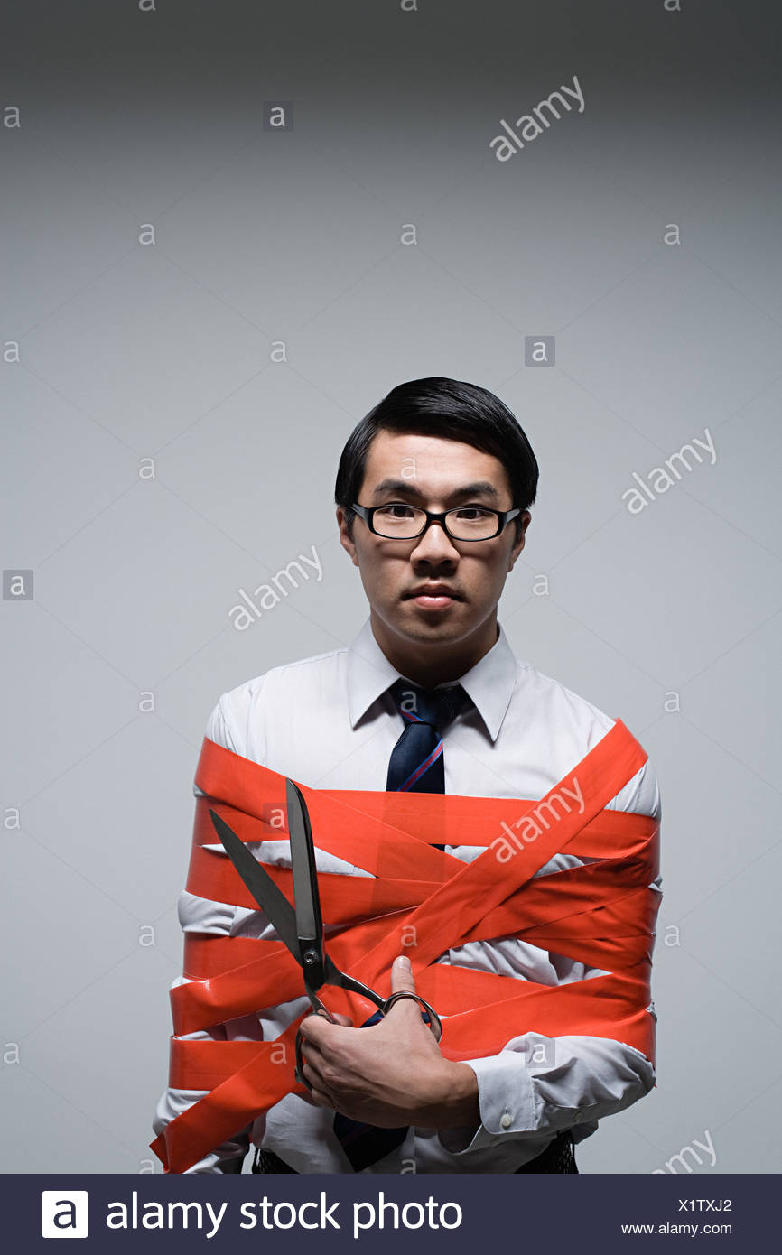 An office worker tied up in red tape Stock Photo