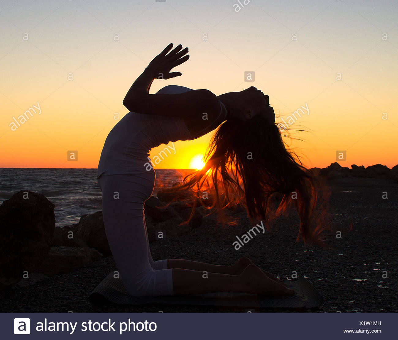 Woman practicing yoga on beach at sunset Stock Photo
