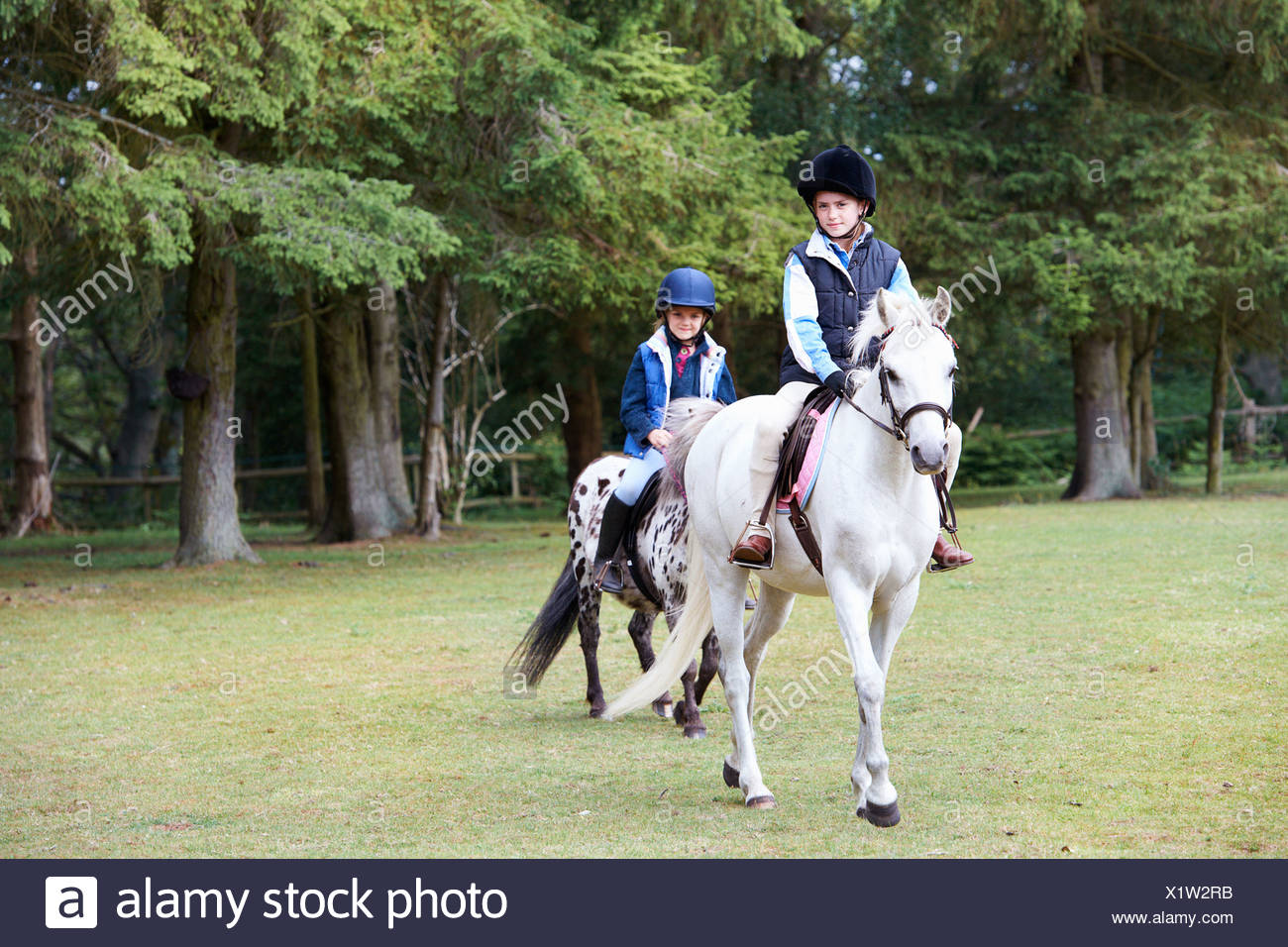 Two girls riding their ponies - Stock Image