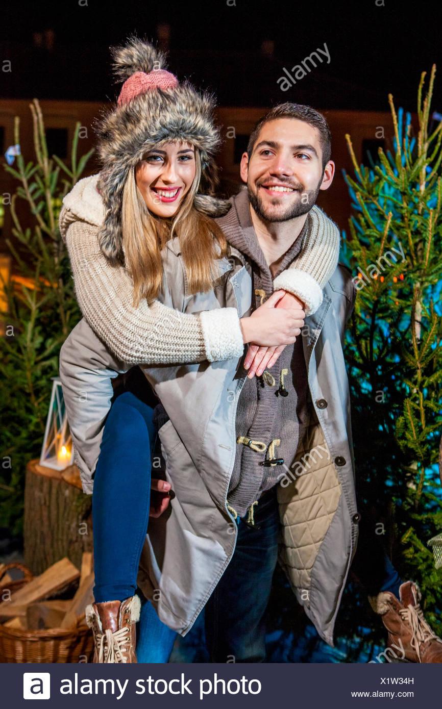 Man giving girlfriend a piggyback ride at Christmas Market - Stock Image