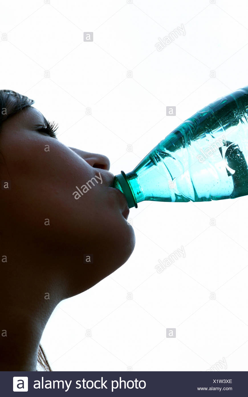 Woman drinking water from a bottle - Stock Image