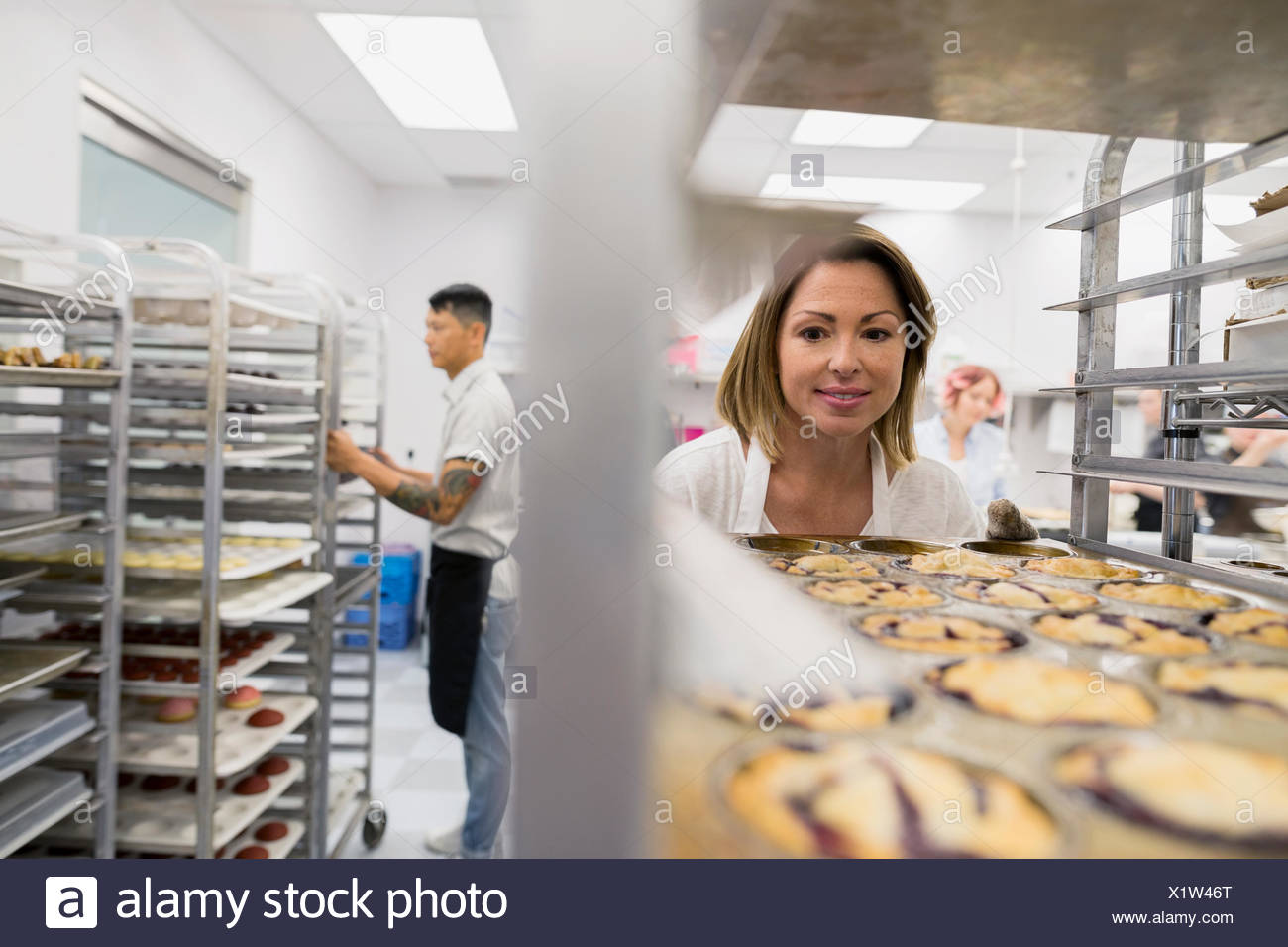 Pastry chef placing muffin tray on rack - Stock Image