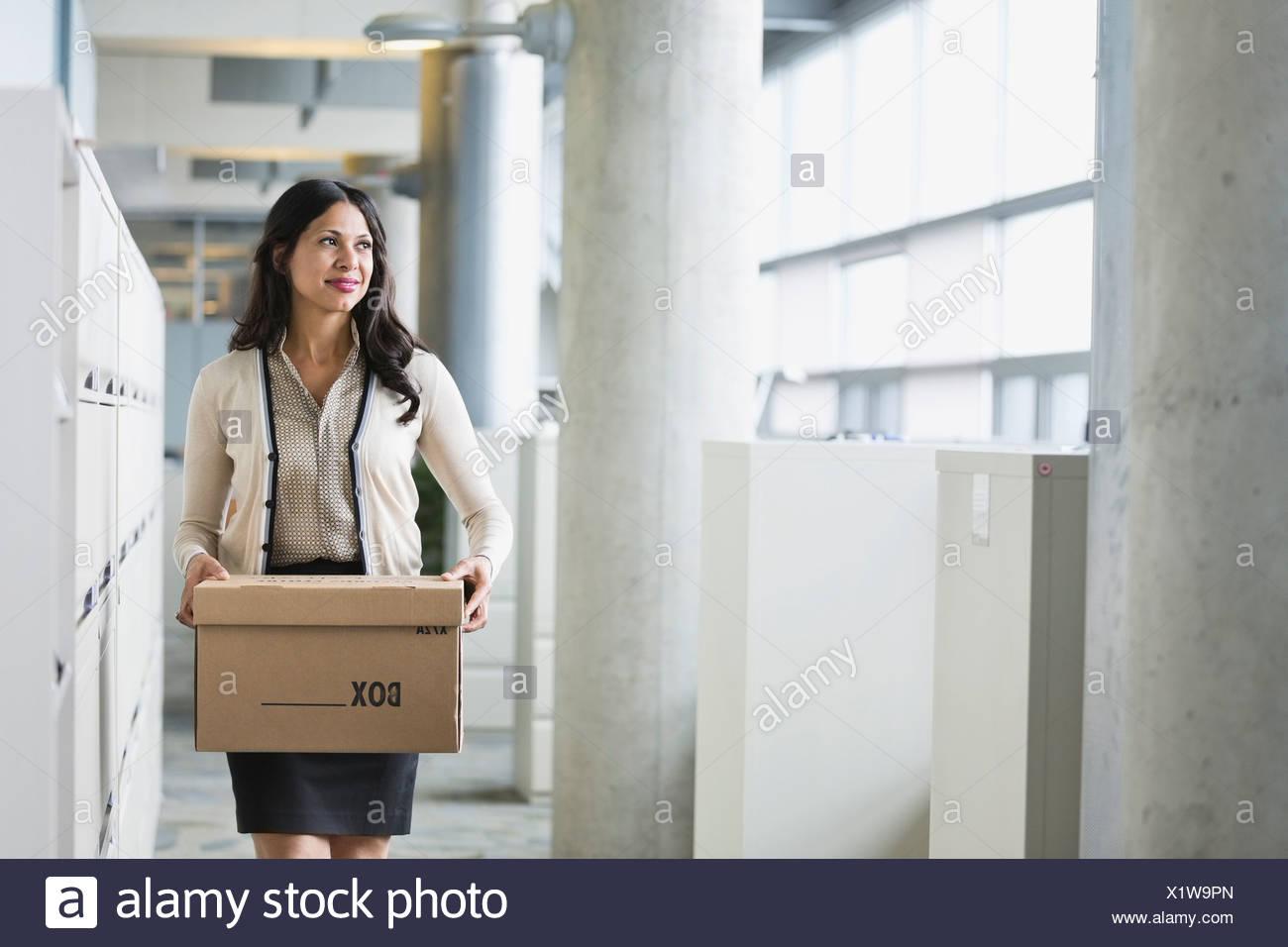 Businesswoman carrying cardboard box - Stock Image