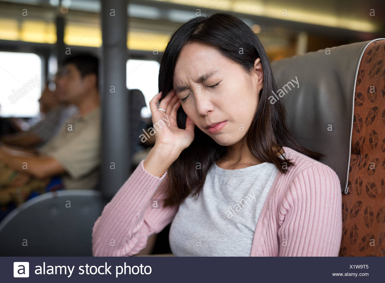 Woman suffer from headache inside the ferry - Stock Image