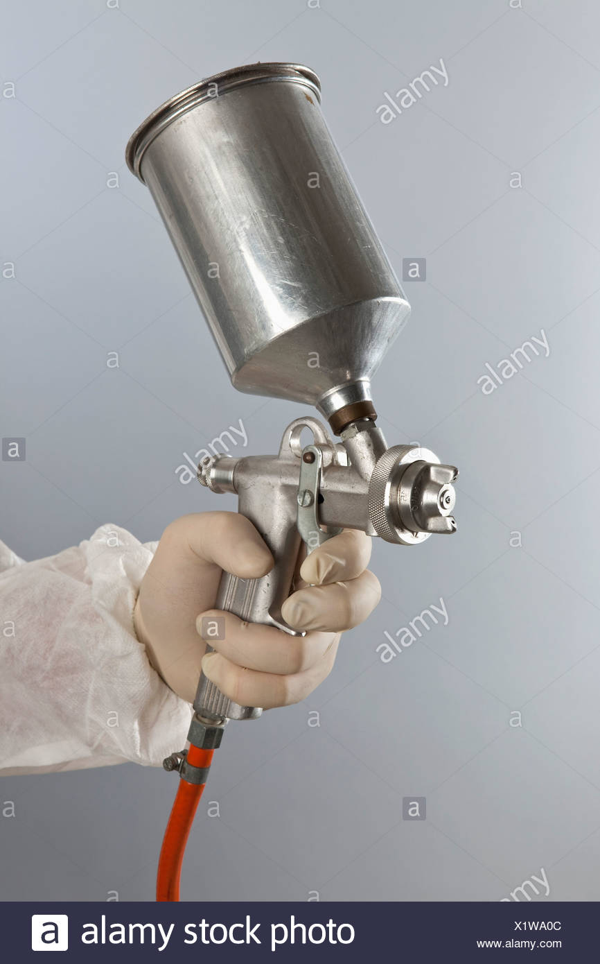 Detail of a person holding a paint spray gun - Stock Image