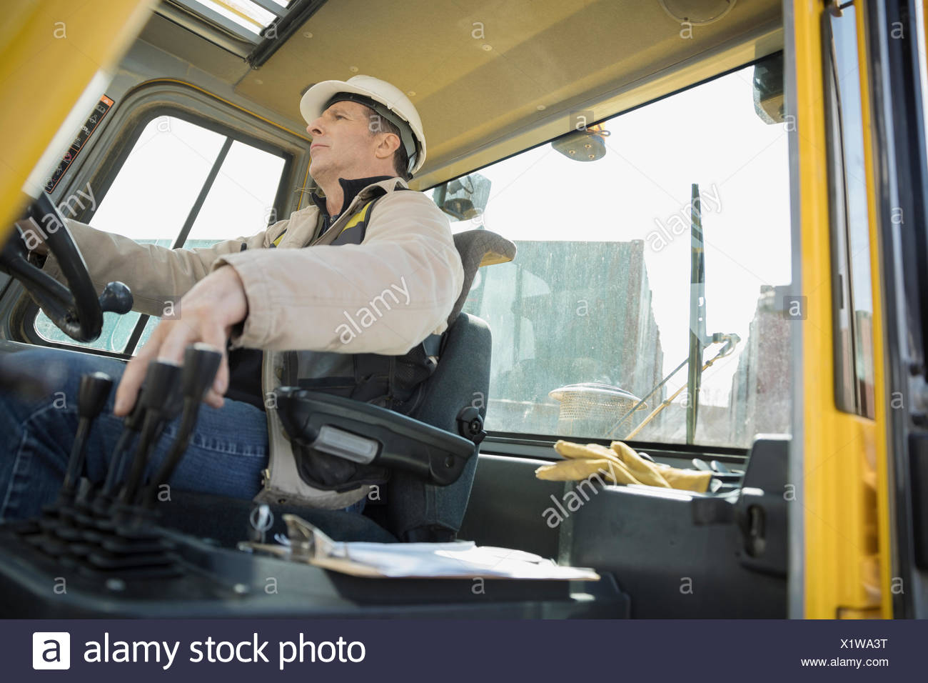 Male worker driving forklift in container yard - Stock Image