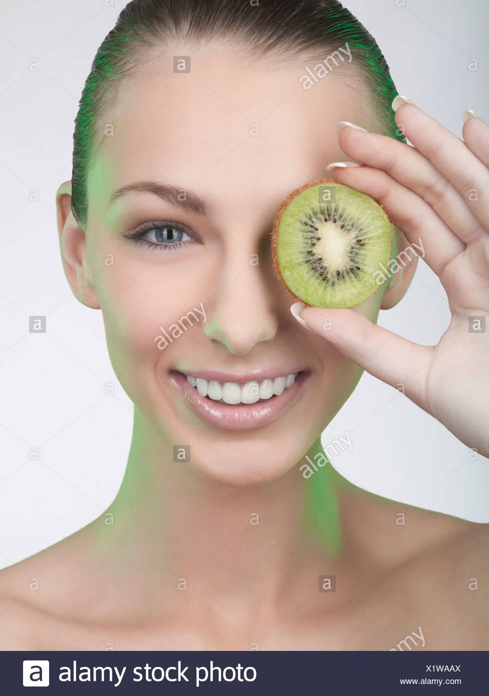 A woman holding a slice of kiwi fruit in front of her eye - Stock Image