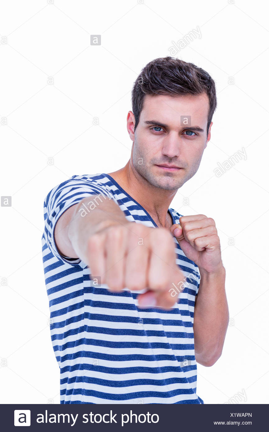 Handsome hipster looking at camera and attacking with his left fist Stock Photo