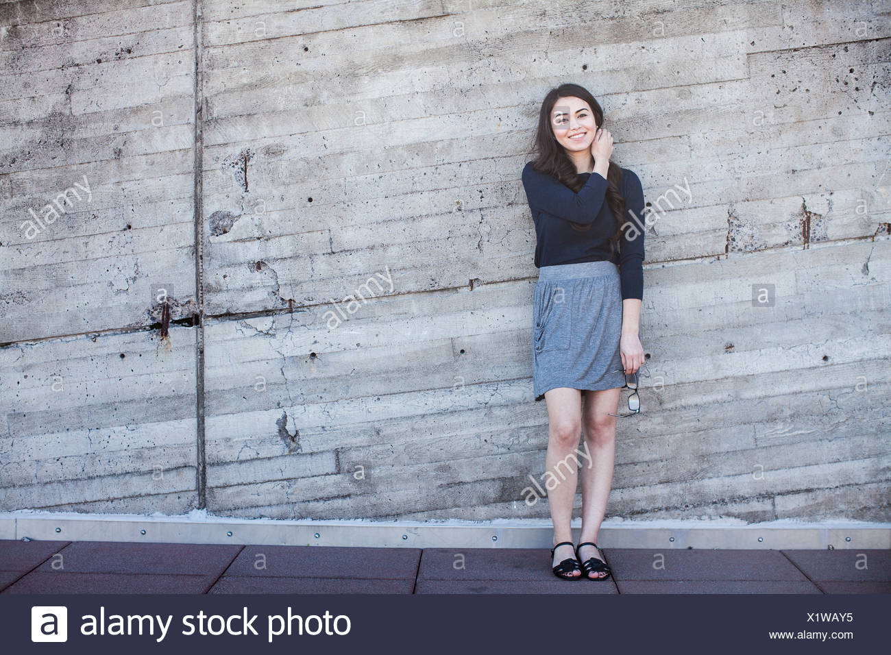 Young woman standing, leaning against wall Stock Photo