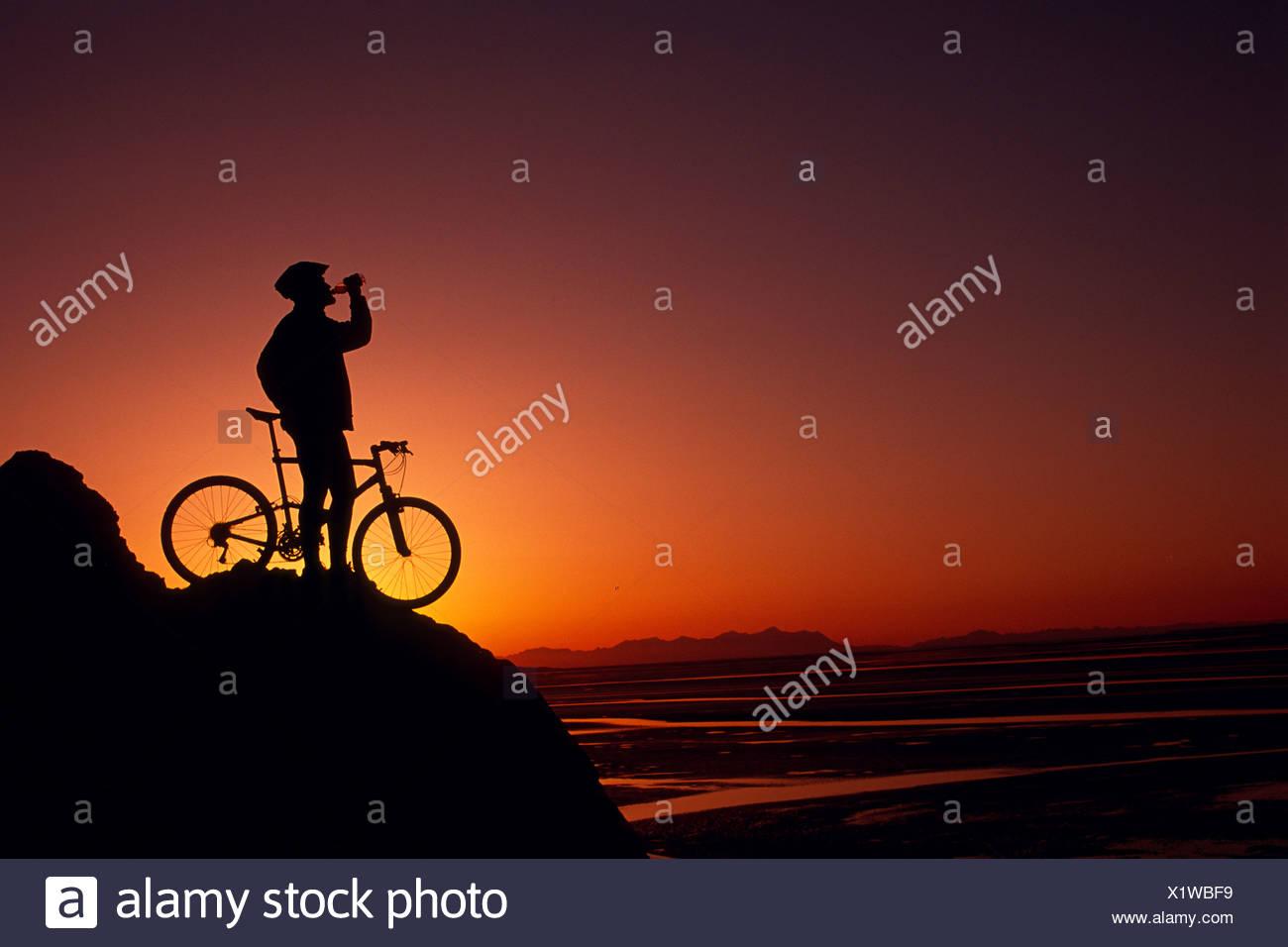 Silhouette of Mountain Biker resting along Turnagain Arm, Alaska - Stock Image