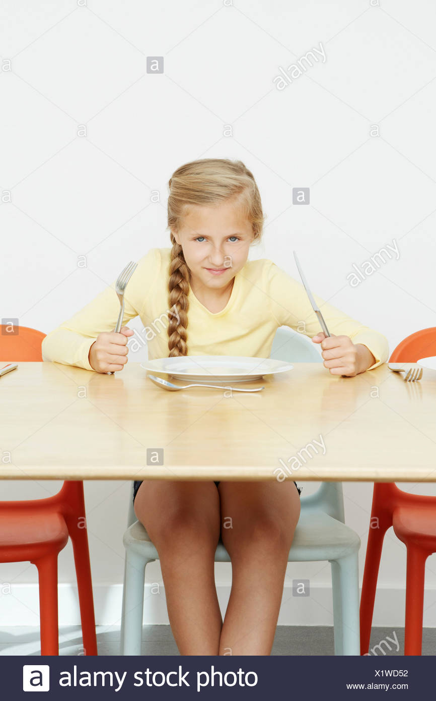 Girl sitting at table with empty plate holding cutlery - Stock Image