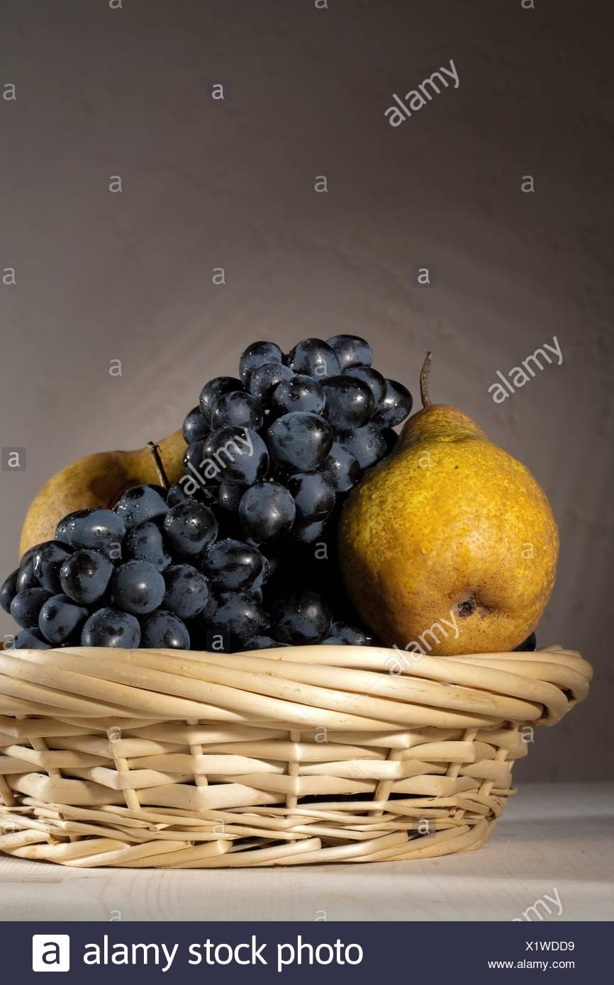 fresh tasty fruit in the bast basket still-life - Stock Image