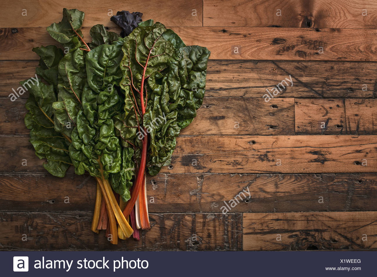 group of red and orange chard leaves with bright coloured stems Organic vegetables freshly picked and placed on a wooden board - Stock Image