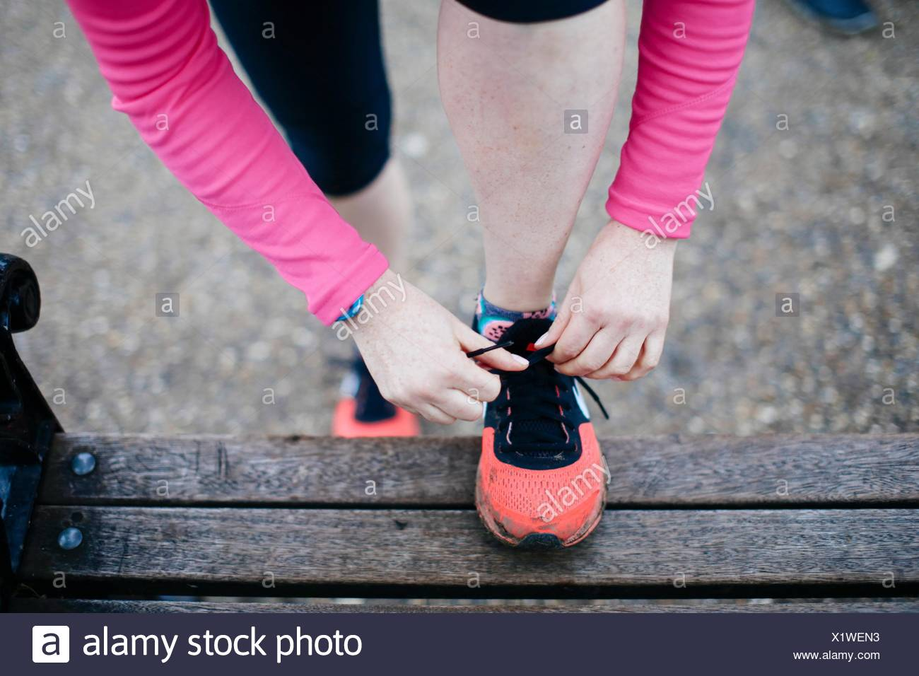 Overhead cropped view of woman tying trainer laces on park bench - Stock Image