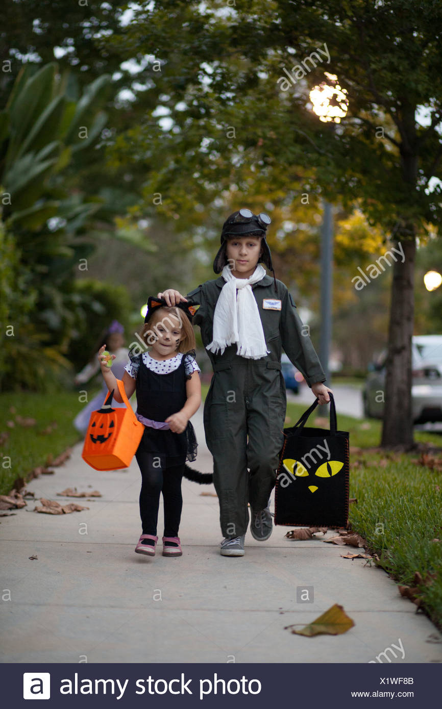 Boy and sister trick or treating in cat and pilot costume walking along sidewalk - Stock Image