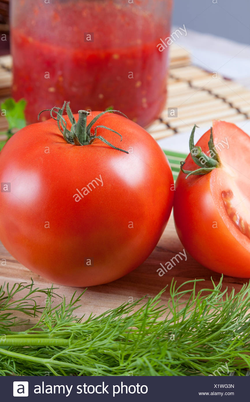 Red tomato on a table with a jar Stock Photo