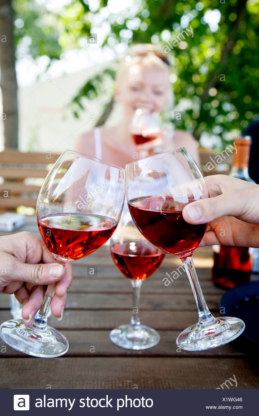 Human hands toasting with wine glasses - Stock Image