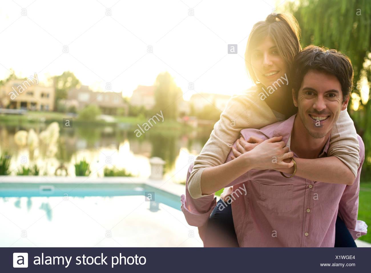 Man giving girlfriend piggyback ride, portrait - Stock Image