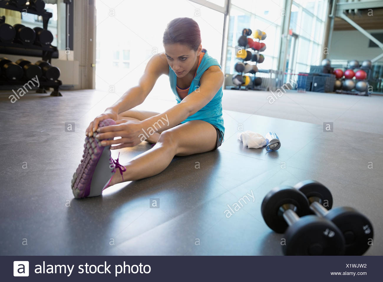 Woman stretching leg in gym - Stock Image