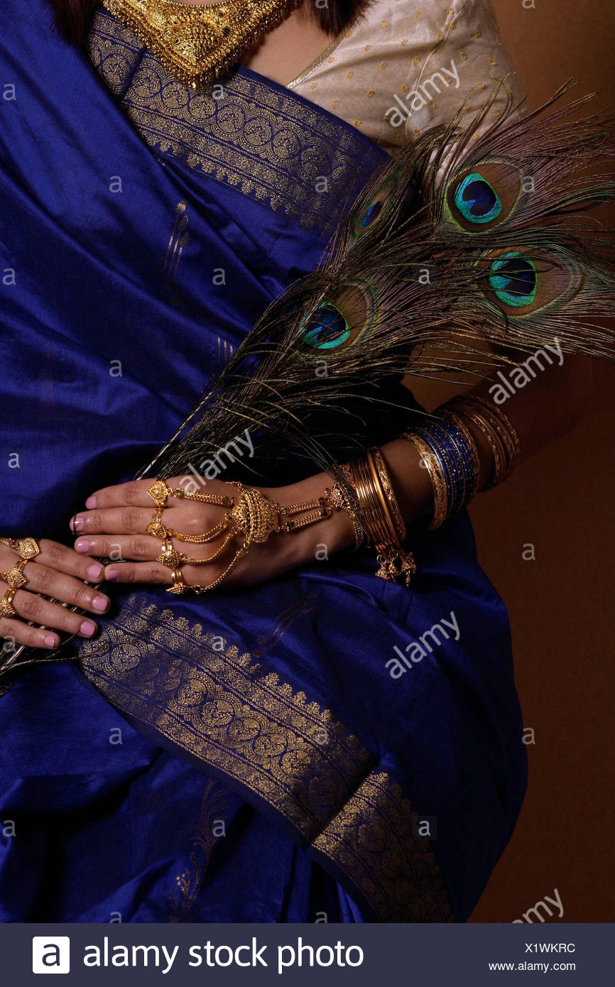 Torso of Indian woman holding peacock feathers - Stock Image