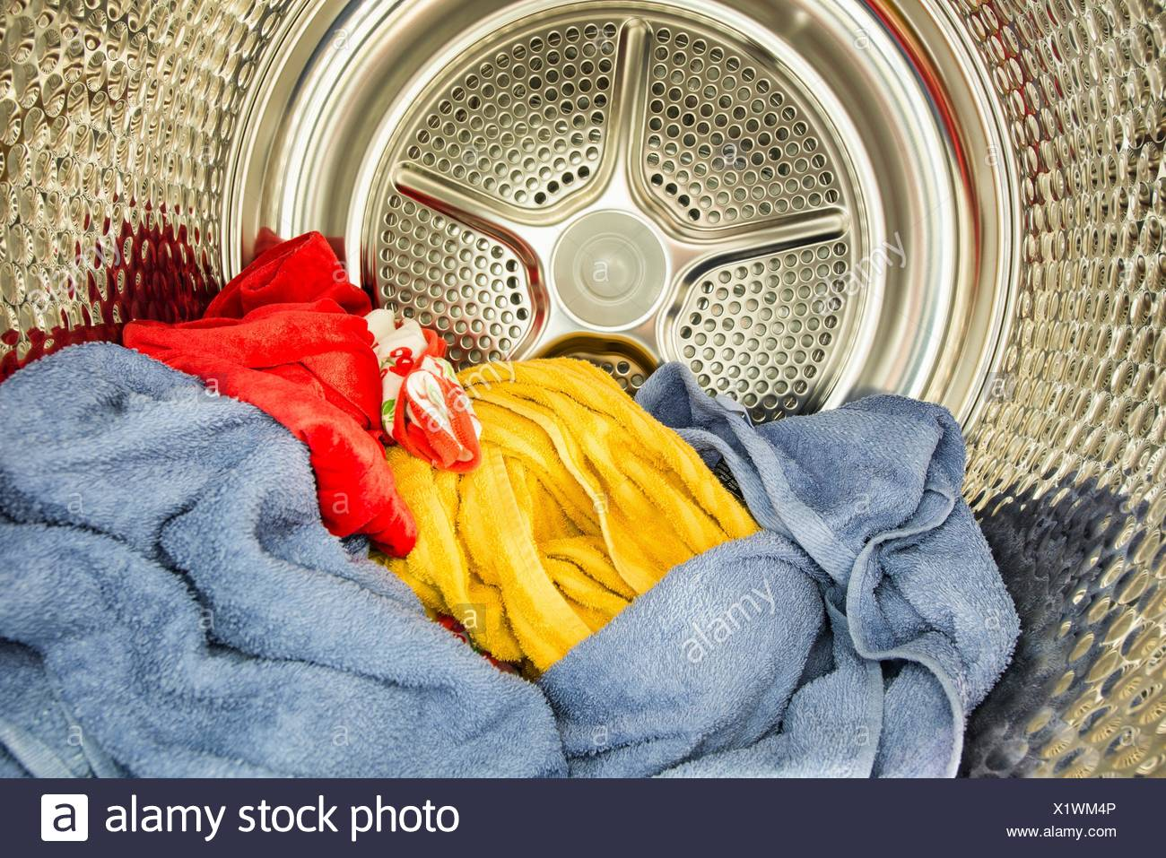 Interior view of tumble dryer with drying clothes. Conceptual image of housework and doing laundry. - Stock Image